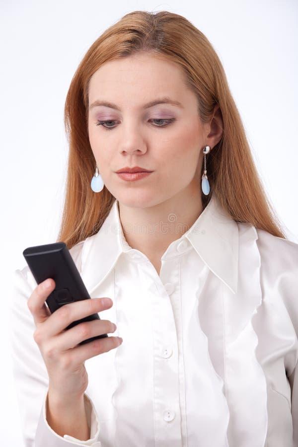 Donna di affari che tiene telefono cellulare fotografia stock libera da diritti