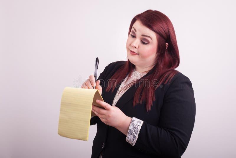 Donna di affari che tiene un blocco note giallo che prende le note che esaminano giù il blocco note fotografia stock