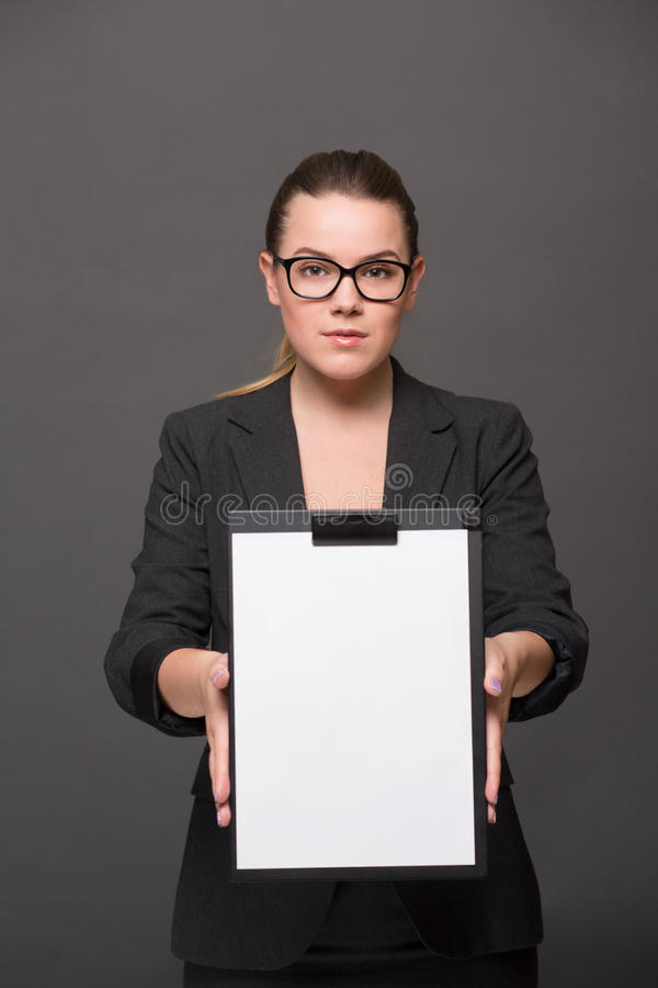 Donna di affari che tiene un bordo di clip fotografia stock libera da diritti