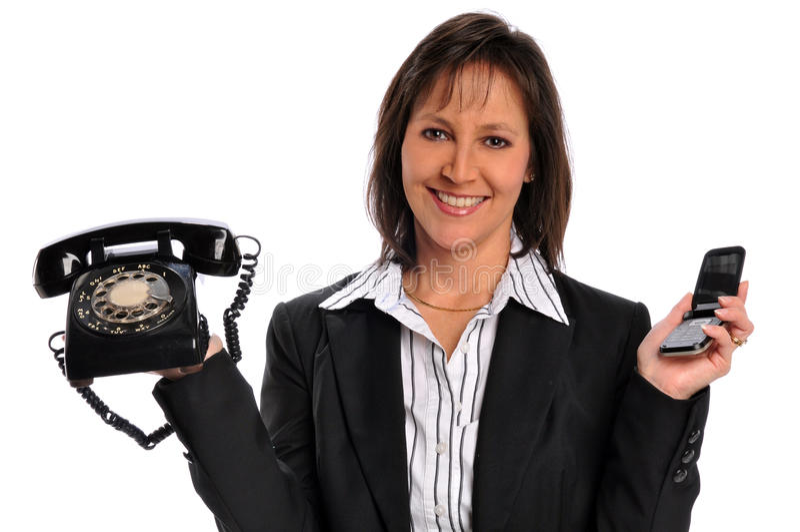 Donna di affari che tiene un telefono dell'annata e una cella immagini stock