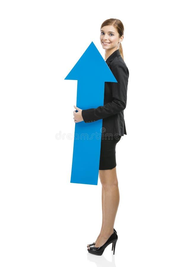 Donna di affari che tiene una freccia blu immagine stock