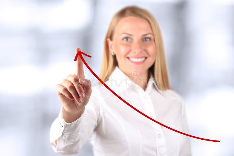 Donna di affari che tocca a mano un grafico virtuale Backgro blu fotografie stock