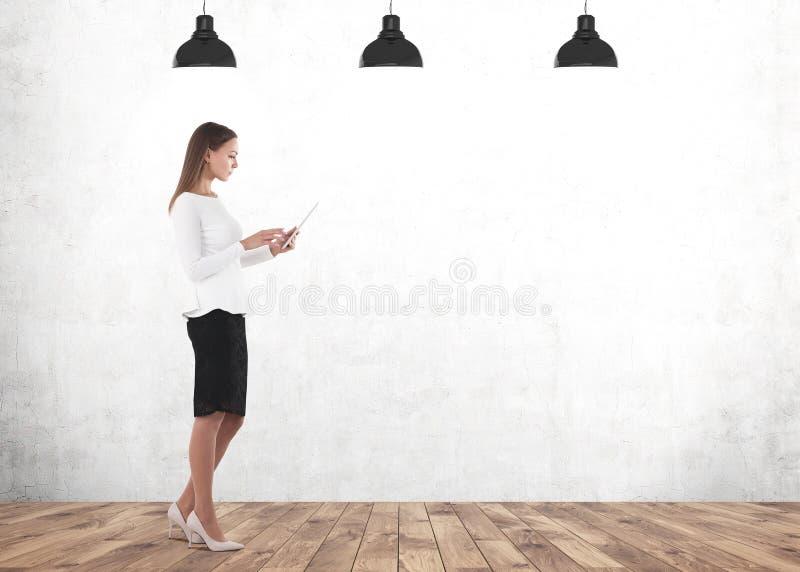 Donna di affari che utilizza compressa nella stanza vuota immagine stock libera da diritti