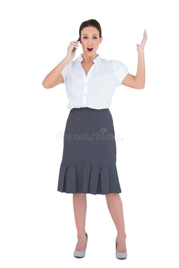 Donna di affari colpita che ha una telefonata immagine stock