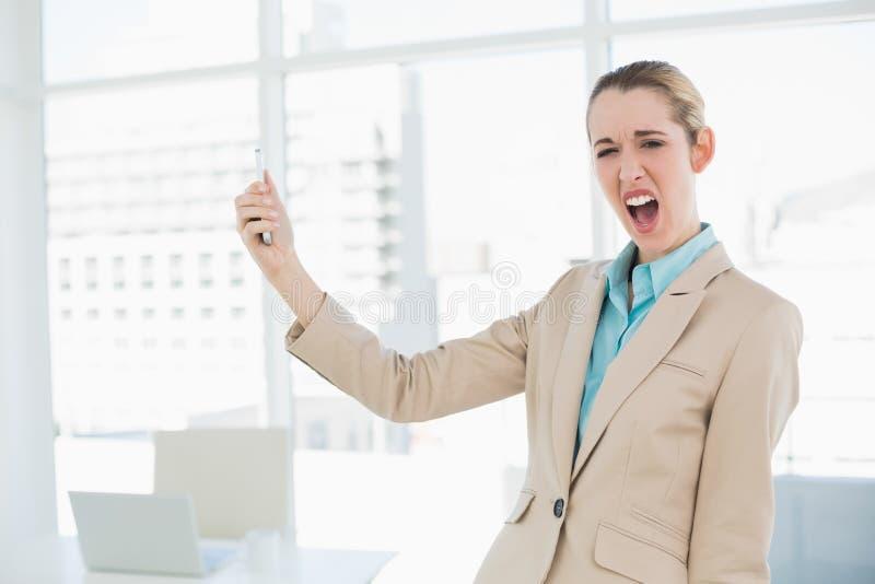 Donna di affari colpita sveglia che tiene il suo smartphone che esamina macchina fotografica fotografia stock