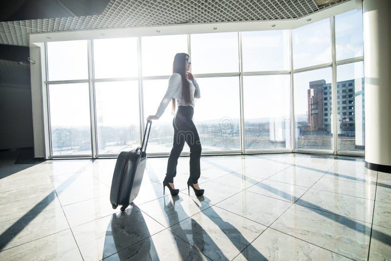 Donna di affari con bagagli nel volo aspettante del terminale di aeroporto internazionale fotografie stock libere da diritti