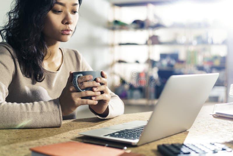 Donna di affari con caffè che esamina lo schermo fotografia stock