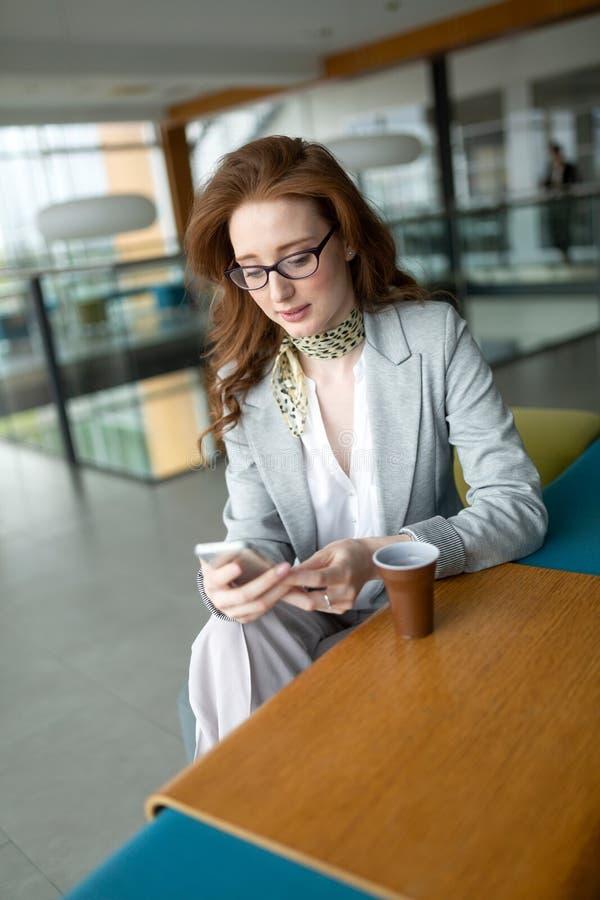 Donna di affari con coffe e parlare sul telefono in ufficio immagine stock libera da diritti