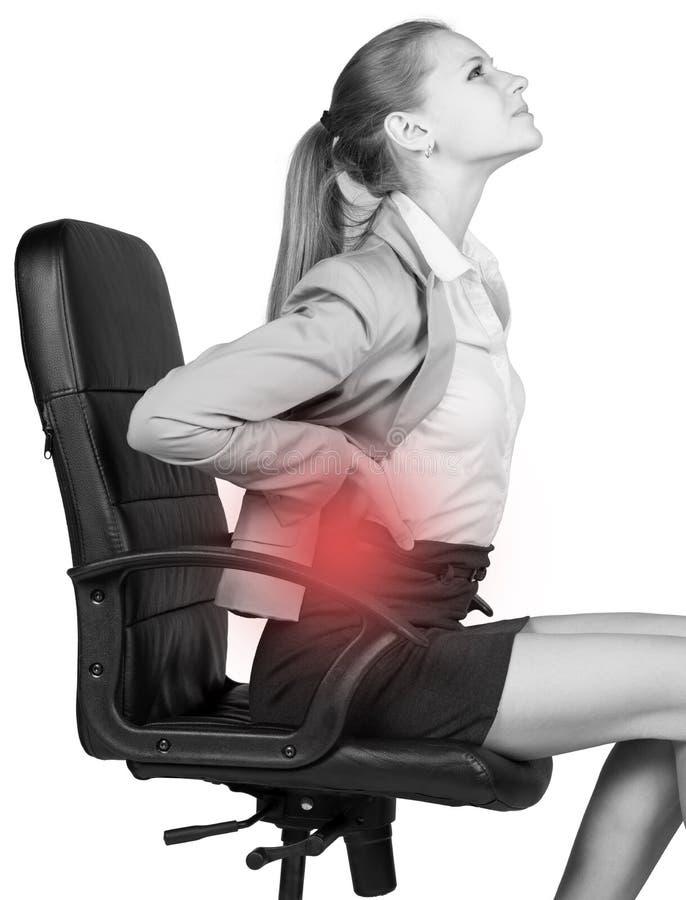 Donna di affari con dolore lombo-sacrale, sedentesi sopra fotografie stock libere da diritti