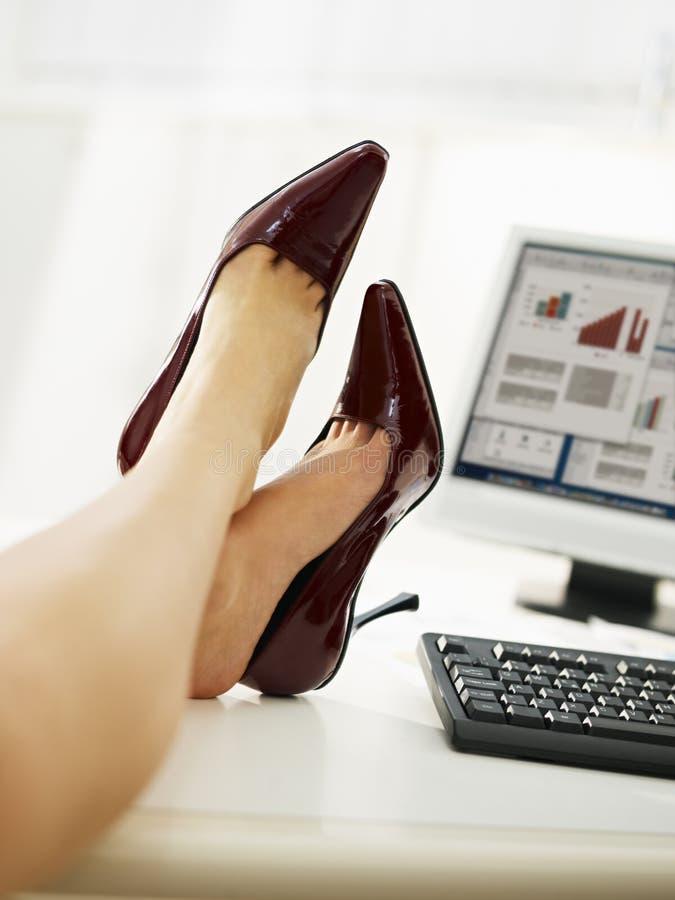 Donna di affari con i piedi sulla tabella che toglie i pattini immagini stock libere da diritti