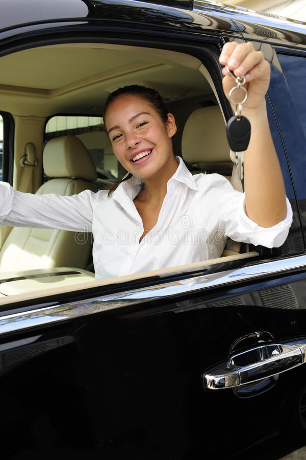 Donna di affari con i tasti di nuovo la sua automobile fotografia stock libera da diritti