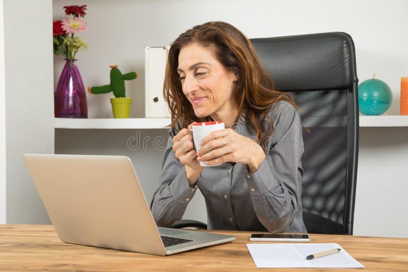 Donna di affari con il computer portatile della lettura del caffè in ufficio fotografie stock libere da diritti
