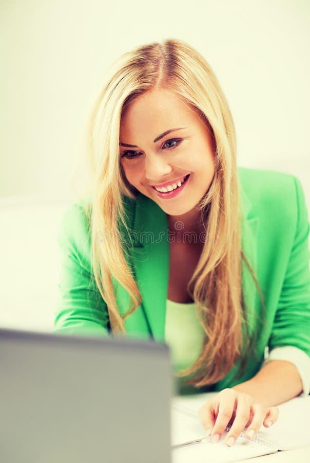 Donna di affari con il computer portatile in ufficio immagini stock