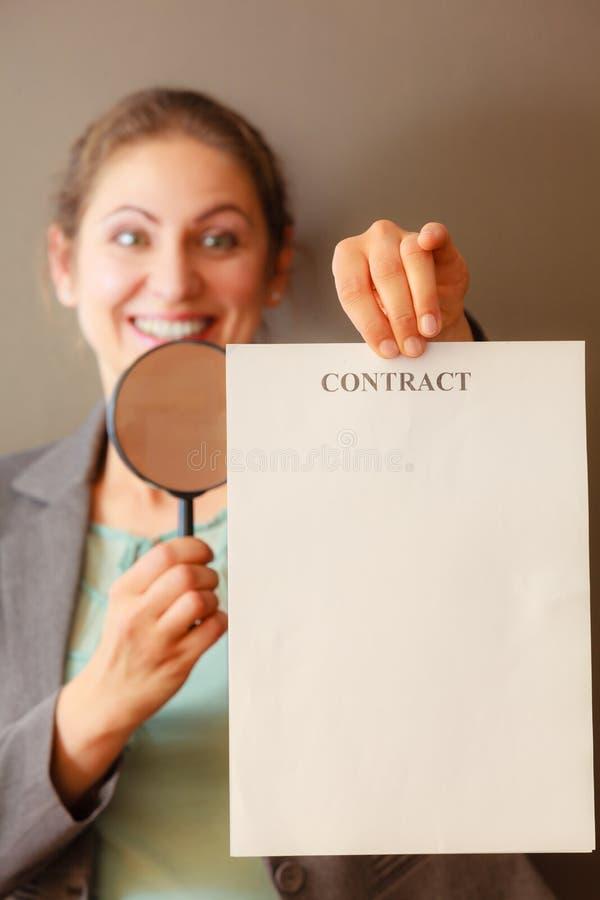 Donna di affari con il contratto e la lente di ingrandimento fotografia stock libera da diritti