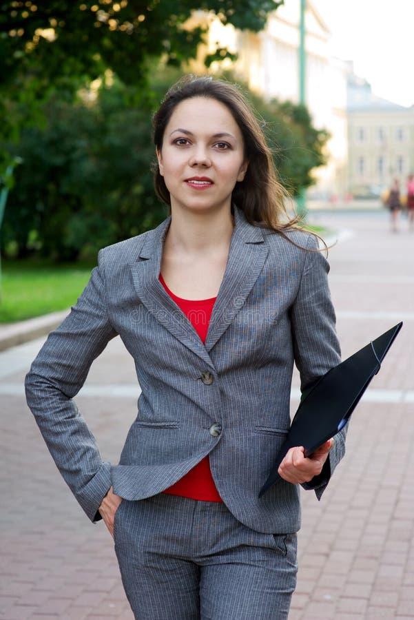 Donna di affari con il dispositivo di piegatura nella città fotografia stock