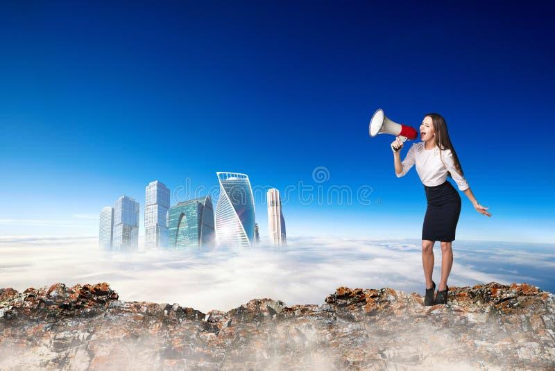 Donna di affari con il megafono sull'orlo di catena montuosa immagine stock
