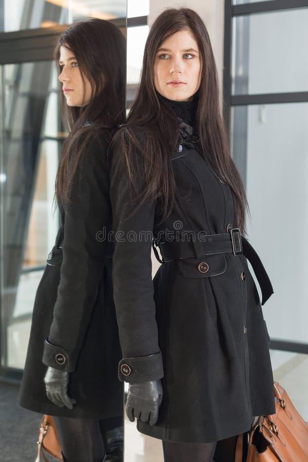 Donna di affari con il supporto della borsa vicino allo specchio fotografia stock libera da diritti