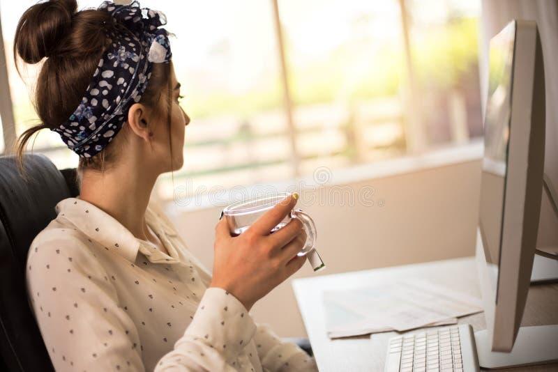 Donna di affari con il tè bevente del computer del pc all'ufficio fotografie stock
