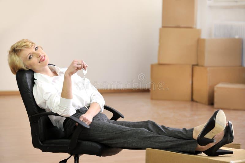 Donna di affari con il tasto al nuovo ufficio fotografie stock