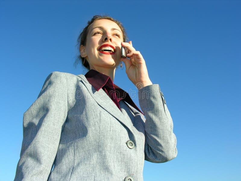 Donna di affari con il telefono su cielo blu immagini stock