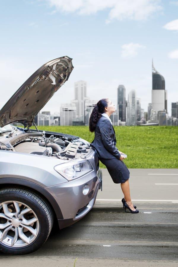 Donna di affari con l'automobile rotta che aspetta un aiuto immagini stock libere da diritti