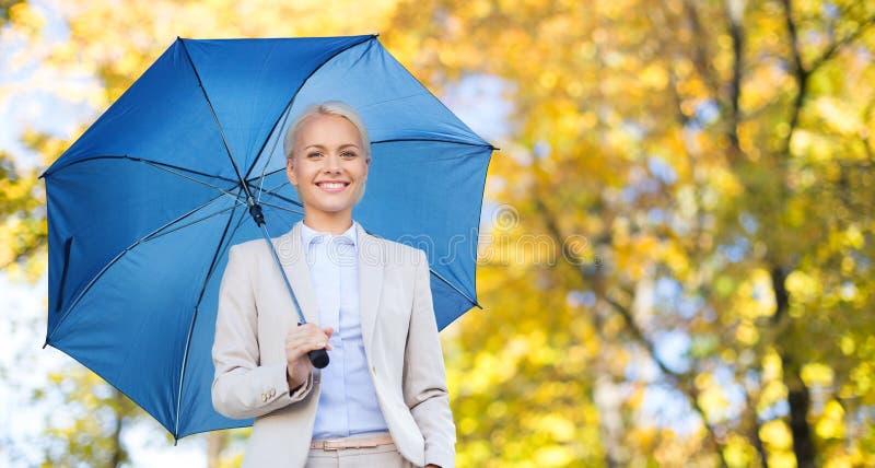 Donna di affari con l'ombrello sopra il fondo di autunno fotografia stock libera da diritti
