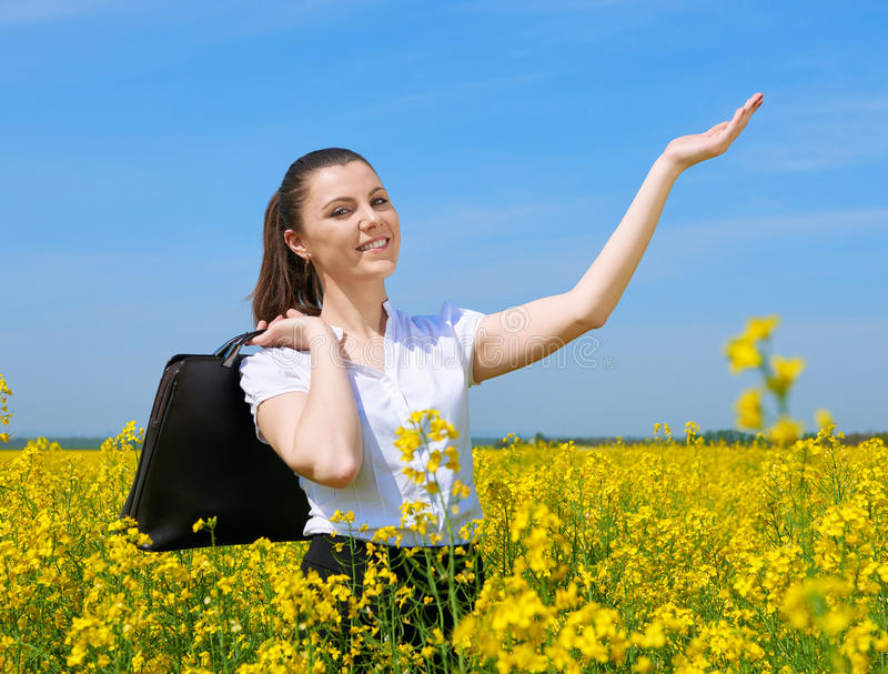 Donna di affari con la cartella che si rilassa in sole di sotto all'aperto del giacimento di fiore Ragazza nel giacimento giallo  fotografia stock