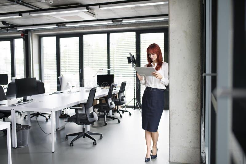 Donna di affari con la compressa nel suo funzionamento dell'ufficio fotografie stock