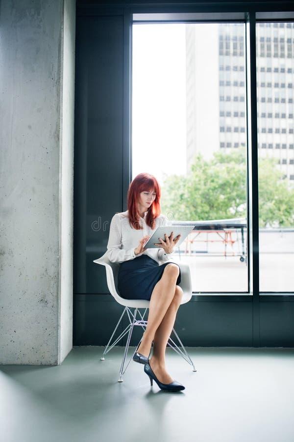 Donna di affari con la compressa nel suo funzionamento dell'ufficio fotografie stock libere da diritti