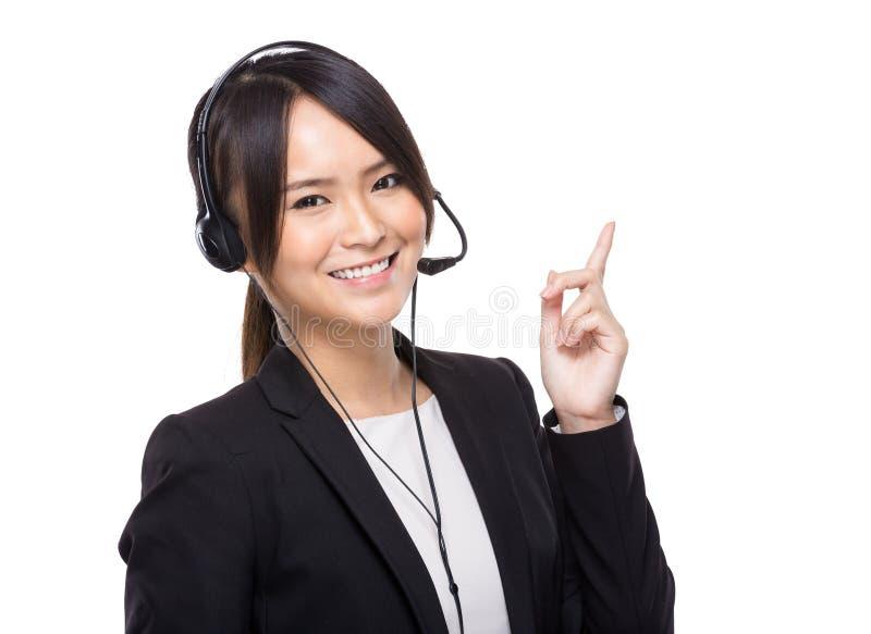 Donna di affari con la cuffia avricolare con il dito su fotografia stock