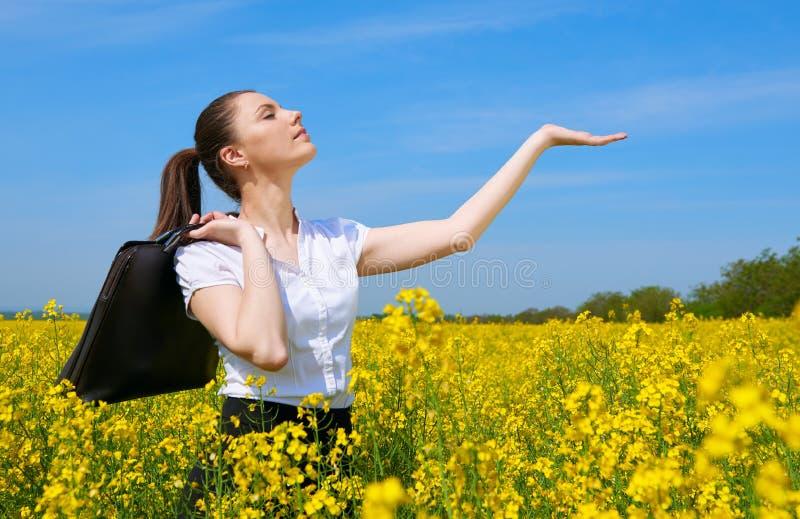 Donna di affari con la palma di manifestazione della cartella da esporre al sole Ragazza nel giacimento di fiore giallo Bello pae fotografia stock libera da diritti