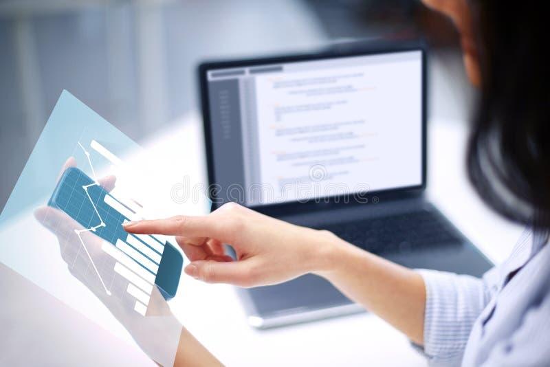Donna di affari con la proiezione e lo smartphone del grafico immagine stock libera da diritti