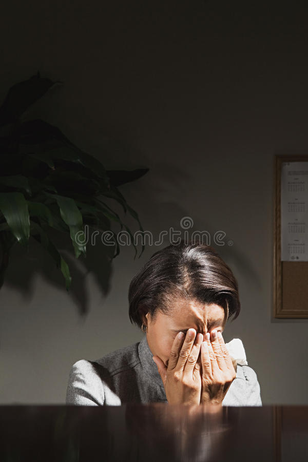Donna di affari con la sua testa in sue mani fotografia stock