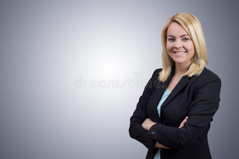 Donna di affari con le mani attraversate su fondo grigio pulito fotografia stock