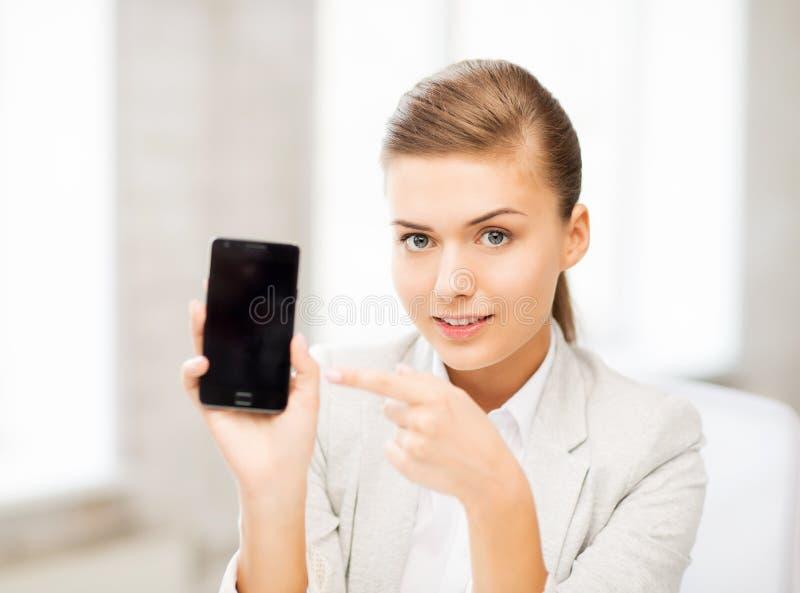 Donna di affari con lo smartphone in ufficio fotografia stock libera da diritti