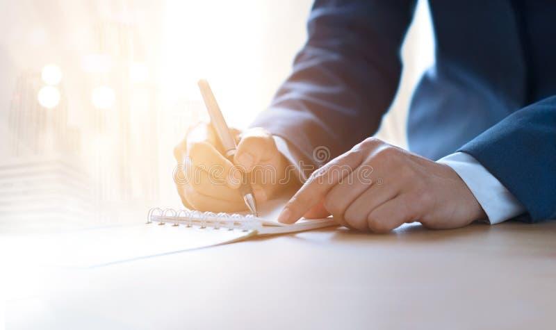 Donna di affari con scrittura della penna sul taccuino nell'illuminazione vibrante fotografia stock libera da diritti