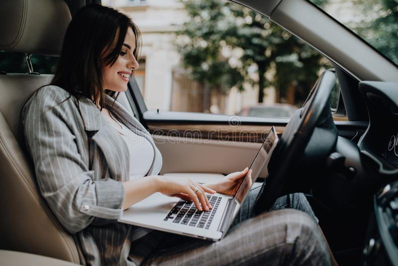 Donna di affari con un computer portatile in sua automobile nella via fotografia stock