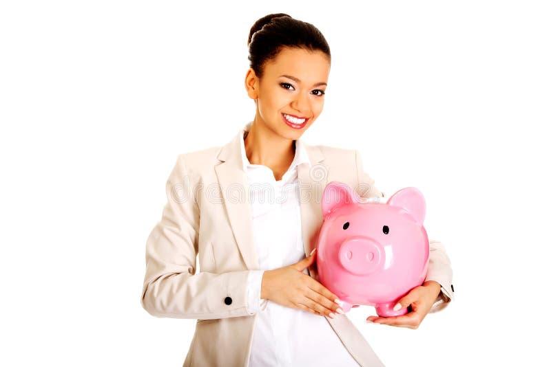 Donna di affari con un porcellino salvadanaio immagini stock