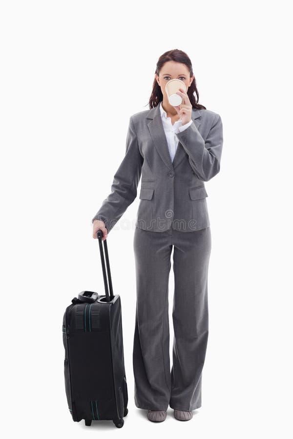 Donna di affari con una valigia che beve un caffè fotografie stock libere da diritti