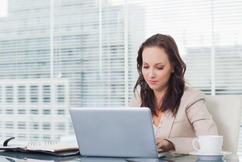 Donna di affari concentrata che lavora al suo computer portatile immagini stock libere da diritti