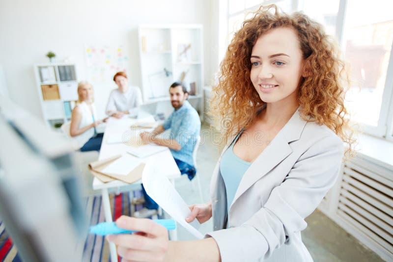 Donna di affari contenta che spiega informazioni ai colleghi immagini stock