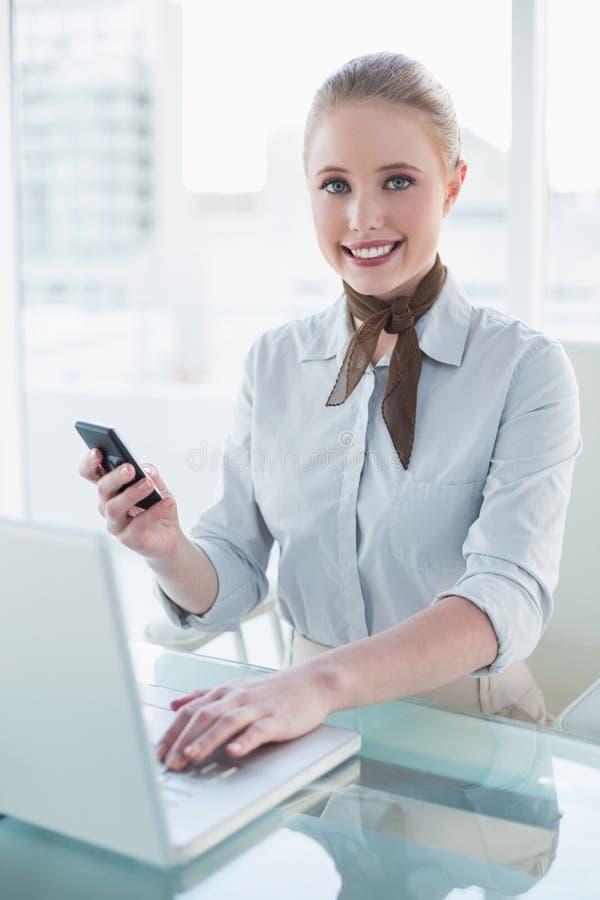 Donna di affari contenta della bionda che per mezzo del computer portatile e dello smartphone fotografia stock libera da diritti