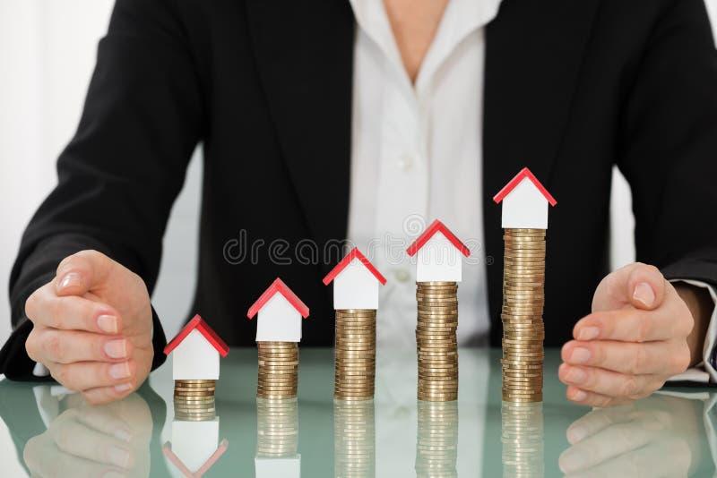 Donna di affari Covering House Models sulle monete impilate immagini stock
