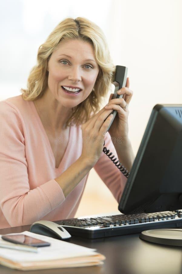 Donna di affari Covering Telephone Receiver allo scrittorio fotografie stock
