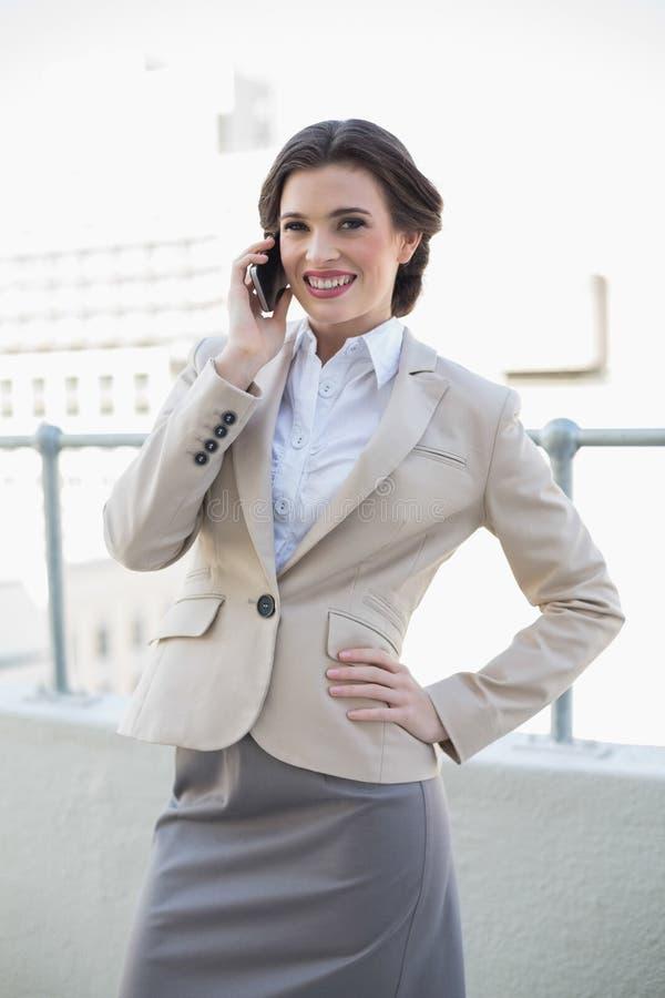 Donna di affari dai capelli marrone alla moda allegra che chiama con il suo telefono cellulare fotografia stock