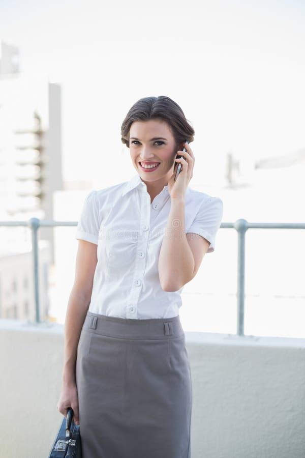 Donna di affari dai capelli marrone alla moda allegra che fa una telefonata immagine stock