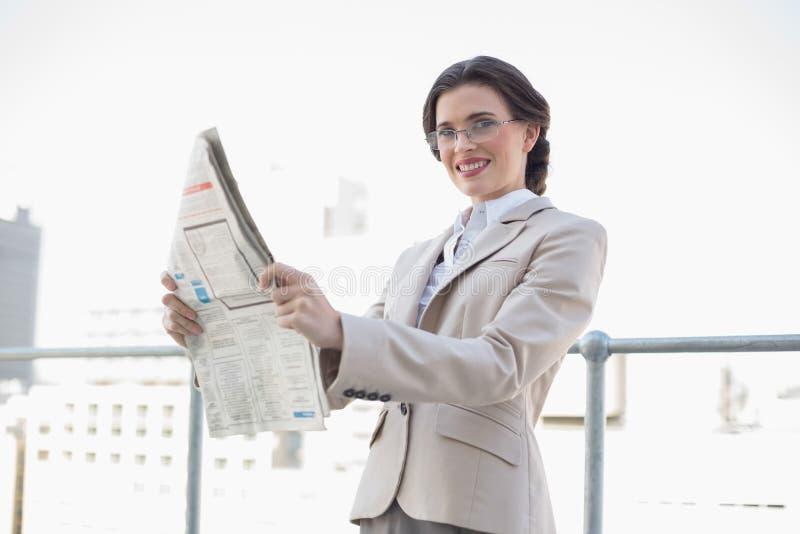 Donna di affari dai capelli marrone alla moda allegra che legge un giornale fotografia stock libera da diritti