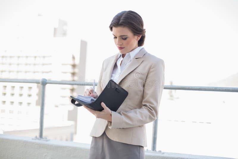 Donna di affari dai capelli marrone alla moda concentrata che riempie il suo programma fotografia stock libera da diritti