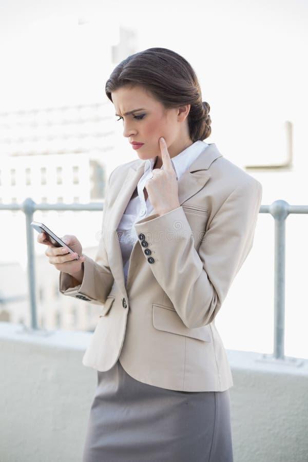 Donna di affari dai capelli marrone alla moda disturbata che esamina il suo telefono cellulare fotografia stock