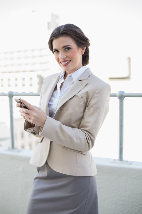 Donna di affari dai capelli marrone alla moda sveglia che per mezzo del suo telefono cellulare immagini stock libere da diritti